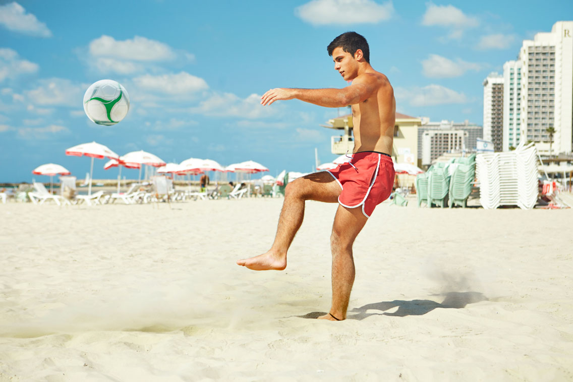 Guy Playing Ball in the Beach