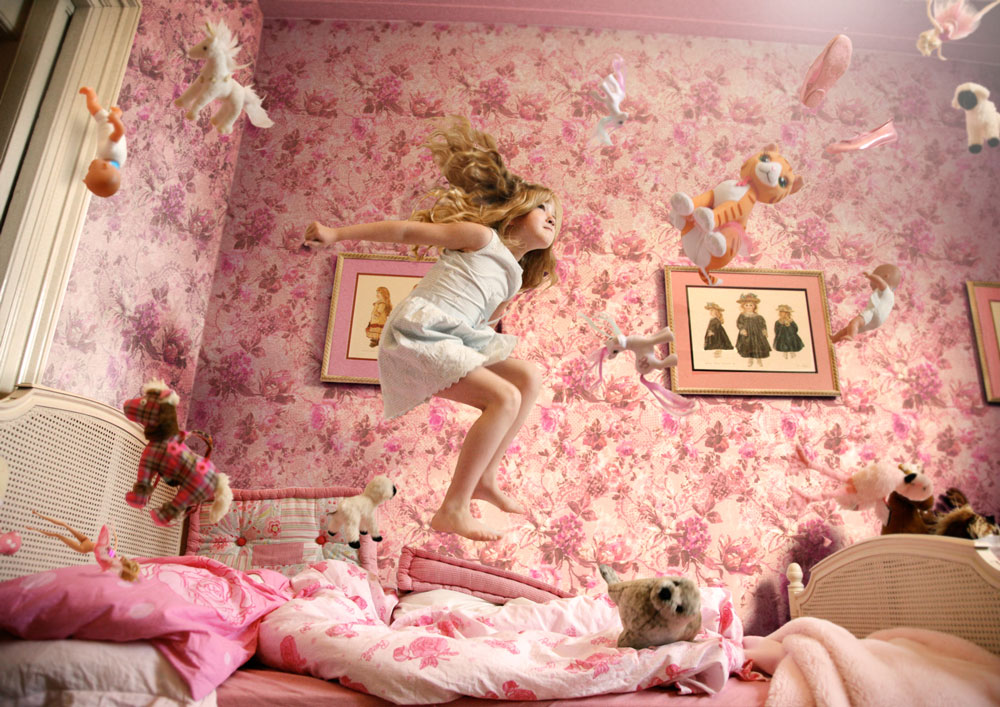 Girl Jumping Up and Down in Bed with Other Stuff Toys