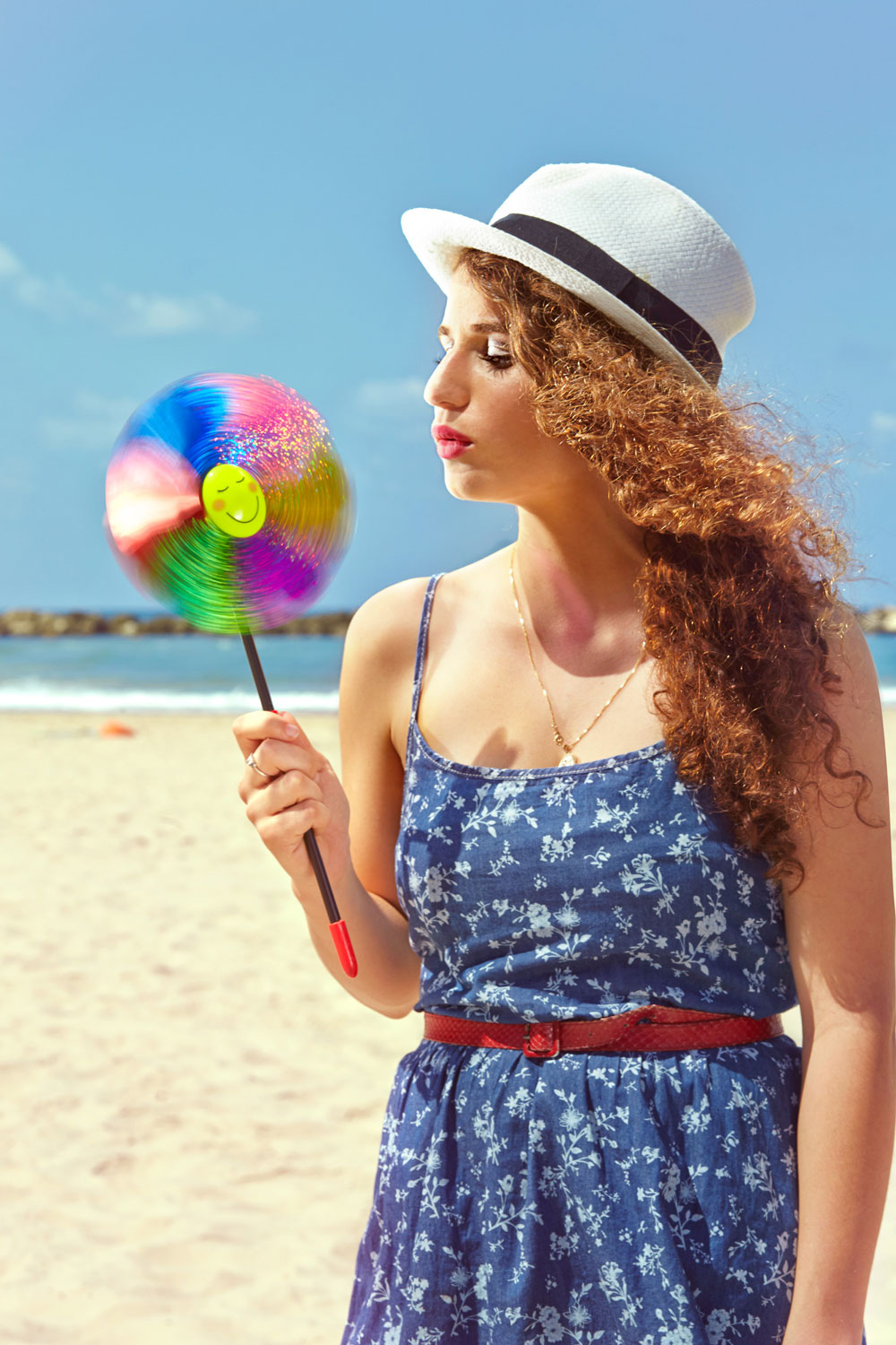 Girl in the Beach Blowing a Color Wheel